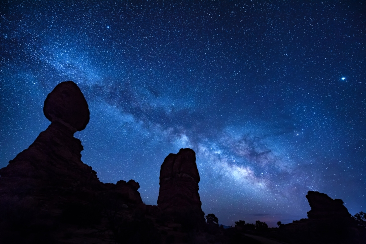 The Milky Way over Balanced Rock sandstone rock formation with t