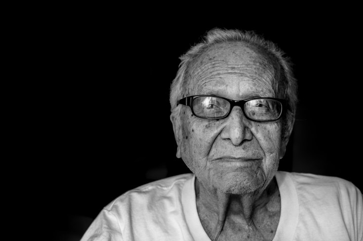 Nica Leon old man tshirt glasses dark background_hermes-rivera-265441-unsplash