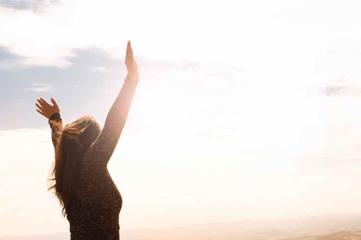 photo of woman raising both hands