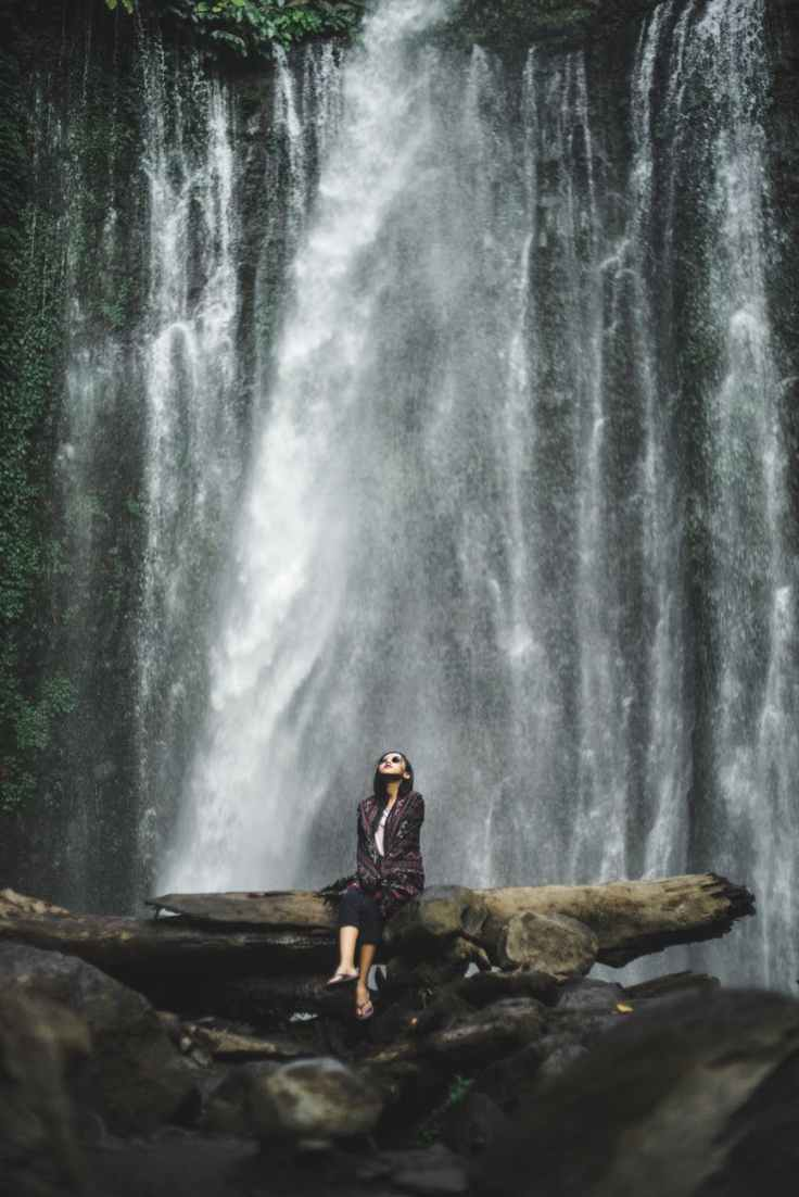 woman sitting fallen tree trunk in front of a waterfalls