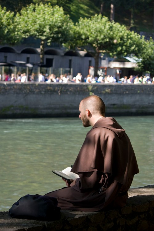 Carmelite friar praying the breviary at Lourdes LawrenceOP Flickr 3862034328